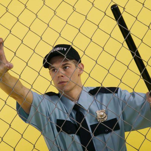 Hombre joven vestido de guardia de seguridad sujetando una verja